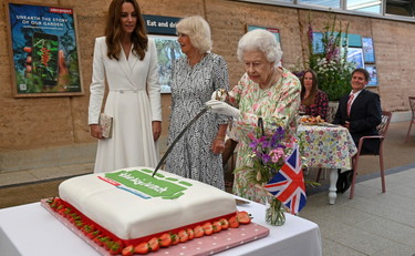 Elizabeth cuts the cake with her sword, and Kate tries to stop it: such irony