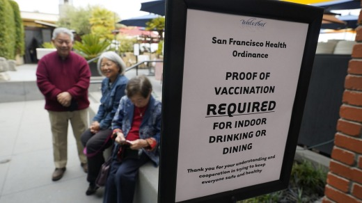 People waiting to have their vaccination records checked before entering a San Francisco restaurant.