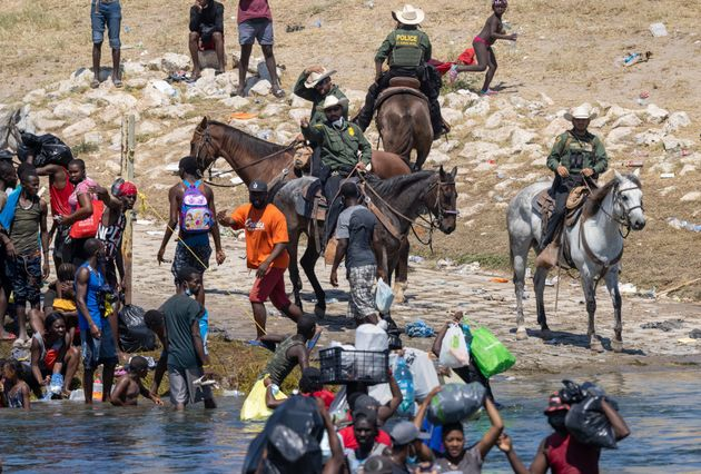 Ciudad Acuna, Mexico - SEPTEMBER 20: US Border Patrol agents interact with Haitian immigrants in…