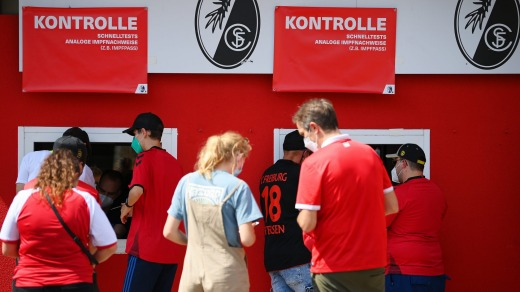 Fans line up to scan their digital vaccination cards before entering a football match in Freiburg im Breisgau, ...