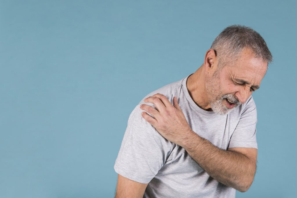 stressed-senior-man-with-shoulder-pain-blue-backdrop